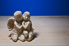 Girl under the wing of an angel, figurine on the table Royalty Free Stock Images