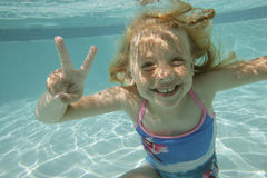 Girl underwater. A little girl swimming underwater in a swimming pool, smiling at the camera Stock Photography