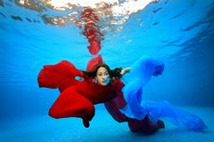 Girl underwater entangled in the red and blue fabrics and looking at the camera. Portrait. Shooting under water. The landscape view Stock Photography