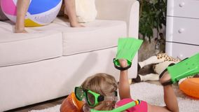 A girl in a underwater mask and flippers swimming in the room stock footage