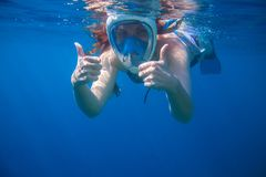 Girl underwater showing thumbs. Snorkeling woman in full face mask. Stock Photography