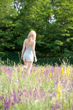 Girl in underwear going away. On meadow Royalty Free Stock Image