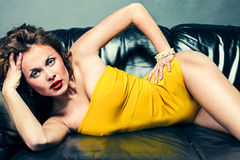 Girl in underwear lying on leather sofa Stock Photos