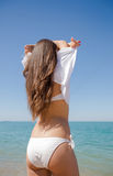 Girl undresses on beach, rear view Royalty Free Stock Photos
