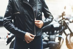 Girl unfastens black leather jacket on background motorcycle in sun flare atmospheric city, hipster biker female hands closeup royalty free stock images
