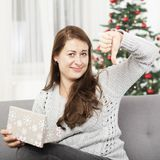 Girl is unhappy about christmas gift and thumb down Royalty Free Stock Photo