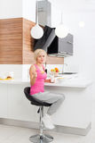 Girl unhappy diet eating healthy cornflakes milk. Young woman sad negative emotion, sitting at table modern kitchen home Royalty Free Stock Image