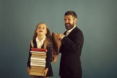Girl in uniform and bearded man. Kid and tutor royalty free stock images