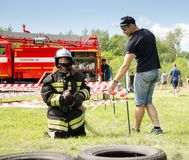 Girl in the uniform of firefighter on obstacles course. Komsomolsk-on-Amur, Russia - August 8, 2016. Public open Railroader`s day. girl in the uniform of royalty free stock photo