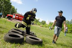 Girl in the uniform of fireman jumps on obstacles course of tire. Komsomolsk-on-Amur, Russia - August 8, 2016. Public open Railroader`s day. girl in the uniform royalty free stock photo
