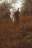 Girl in uniform leading a horse through field of flowers Royalty Free Stock Photo