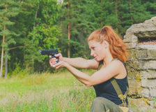 Girl in uniform looking for the target from the gun Royalty Free Stock Image