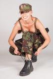 Girl in uniform sitting tying shoelaces. Gray background. Royalty Free Stock Photo