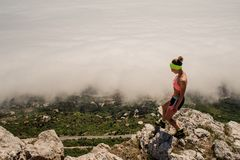 Girl in uniform, sneakers stands on a stone looks down at the valley in the fog stock images