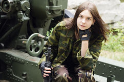 Girl in uniform with a submachine gun sitting on an artillery gun carriage royalty free stock image