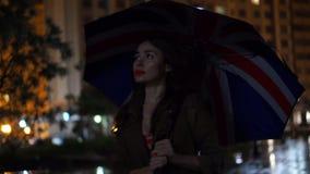 Girl with Union Jack umbrella walking at rainy night, slow motion video. Beautiful brunette girl with umbrella walks at rainy night stock video footage