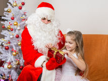 Girl unleashes red ribbon gift that keeps Santa Claus in the hands of Stock Images