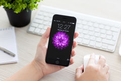Girl unlock iPhone 6 Space Gray over the table Stock Photography
