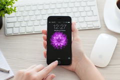 Girl unlock iPhone 6 Space Gray over the table Stock Image