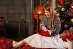 Girl unpacks Christmas gift. Sweetheart attractive woman unpacking a Christmas gift Stock Image