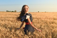 The girl with the unraveling hair spins in the field stock photos