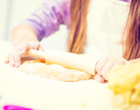 Girl unrolls cookie dough Royalty Free Stock Photo