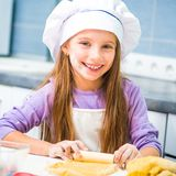Girl unrolls cookie dough Stock Images