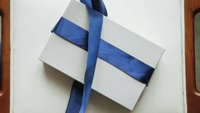 Girl unties the ribbon on blue striped box. Of clothes stock footage