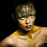 Girl with unusual makeup crocodile. Portrait of a young girl with an unusual makeup aggressive alligator Royalty Free Stock Image