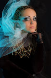 A girl with an unusual theatrical makeup. In the dark tones Royalty Free Stock Image