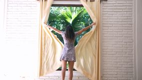 Girl in dress unveil the curtains in the morning. Girl unveil the curtains in the morning stock photography