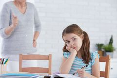 Girl unwilling to do homework. Girl sitting at the desk but unwilling to do homework Royalty Free Stock Image