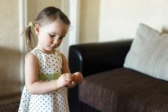 Girl unwrapping candy at home. Sweet home stock photography
