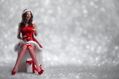 Girl unwrapping christmas present. Beautiful young pin-up girl in santa dress unwrapping a christmas present on glitter bokeh background Royalty Free Stock Image