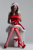 Girl unwrapping christmas present. Beautiful young pin-up girl in santa dress unwrapping a christmas present Stock Photo