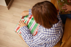 Girl unwrapping a Christmas present Royalty Free Stock Photography