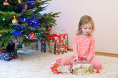 A girl unwrapping presents on Christmas morning Stock Image