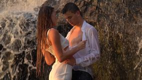 The girl unzips the guy`s shirt standing under the waterfall, slow motion shooting. A girl unbuttons a white shirt, standing under a waterfall among the rocks stock footage