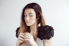The girl up to something, cunning. Beautiful girl up to something, cunning with hooded eyes, a bright make-up, raised his hands, black shoulders, Paone feathers Royalty Free Stock Image
