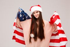 Girl upset posing with American flag on gray background royalty free stock images