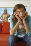 Girl upset on sofa, mother in the background. Royalty Free Stock Photos