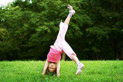 Girl upside-down. Joyful girl in pink upside-down Royalty Free Stock Photography