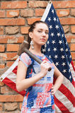 Girl with USA flag and a hammer Stock Image
