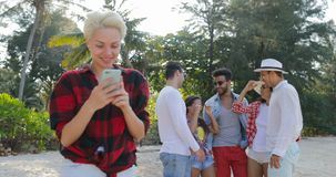 Girl Use Cell Smart Phone Chatting Online Over Young People Group Talking In Tropical Palm Tree Park. Slow Motion 60 stock video footage