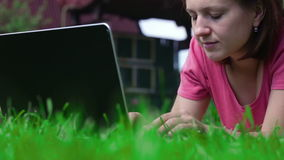 Girl use laptop, lying on the lawn stock footage