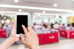 Girl use mobile phone and blur image inside the mall. Royalty Free Stock Photos