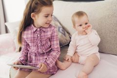 Girl Use Tablet and Sit with Young Sister Indoors royalty free stock images