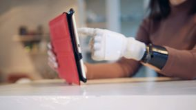 Person types on a tablet with bionic hand, close up. Girl uses a bionic prosthesis to type on a tablet stock footage