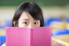 Girl uses a book to cover her face Royalty Free Stock Photography