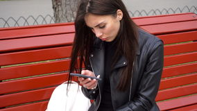Girl uses a cell phone on a bench in the Park stock footage